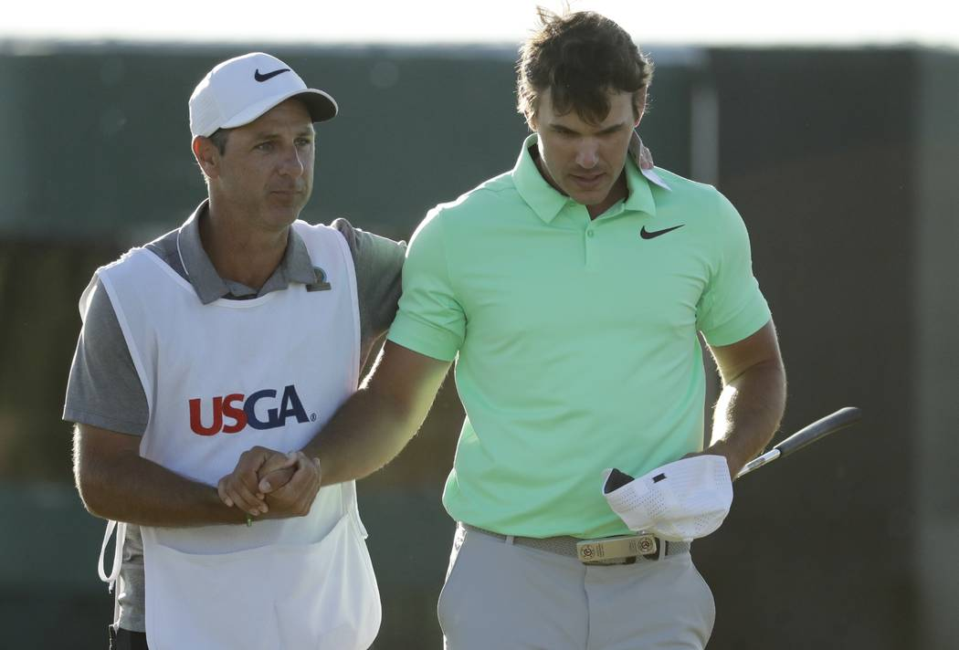 Brooks Koepka, right, is congratulated by caddie Ricky Elliot after the fourth round of the U.S. Open golf tournament Sunday, June 18, 2017, at Erin Hills in Erin, Wis. (AP Photo/Charlie Riedel)
