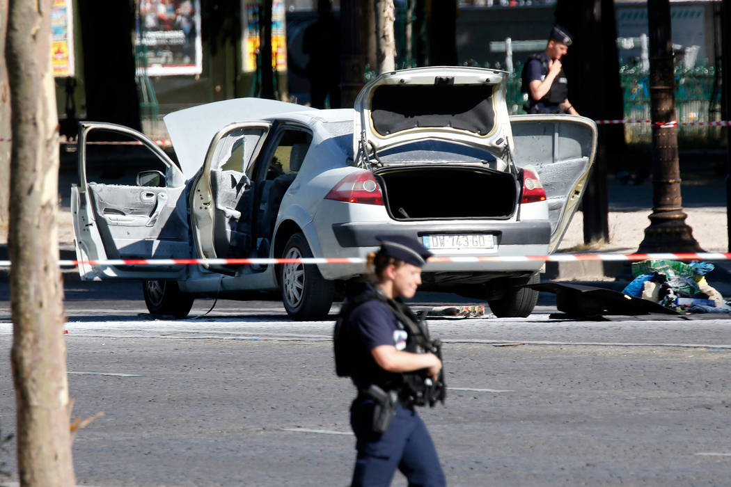 Police secure the area near a burned car at the scene of an incident in which it rammed a gendarmerie van on the Champs-Elysees Avenue in Paris, France, June 19, 2017. A driver appeared to deliber ...