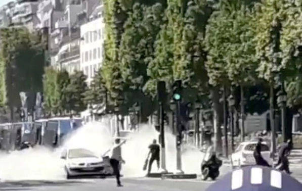 French police officers engage with a suspect outside a car at the Champs Elysees avenue in Paris, France June 19, 2017 in this still image obtained from social media. (Eugenio Marcillo via Reuters)