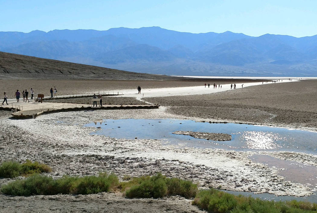 Tourists walk around Badwater in Death Valley National Park in California on Monday, June 12, 2017. Badwater, at 282 feet below sea level, is the lowest point in the Western Hemisphere. It is ofte ...