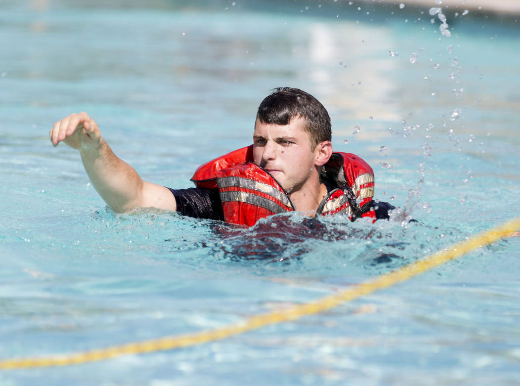 Firefighter Matt Hibschman reaches to a rope during a simulation of a rescue in the wash and churning water conditions at Wet'n'Wild Las Vegas in Las Vegas, Wednesday, June 21, 2017. Elizabeth Bru ...