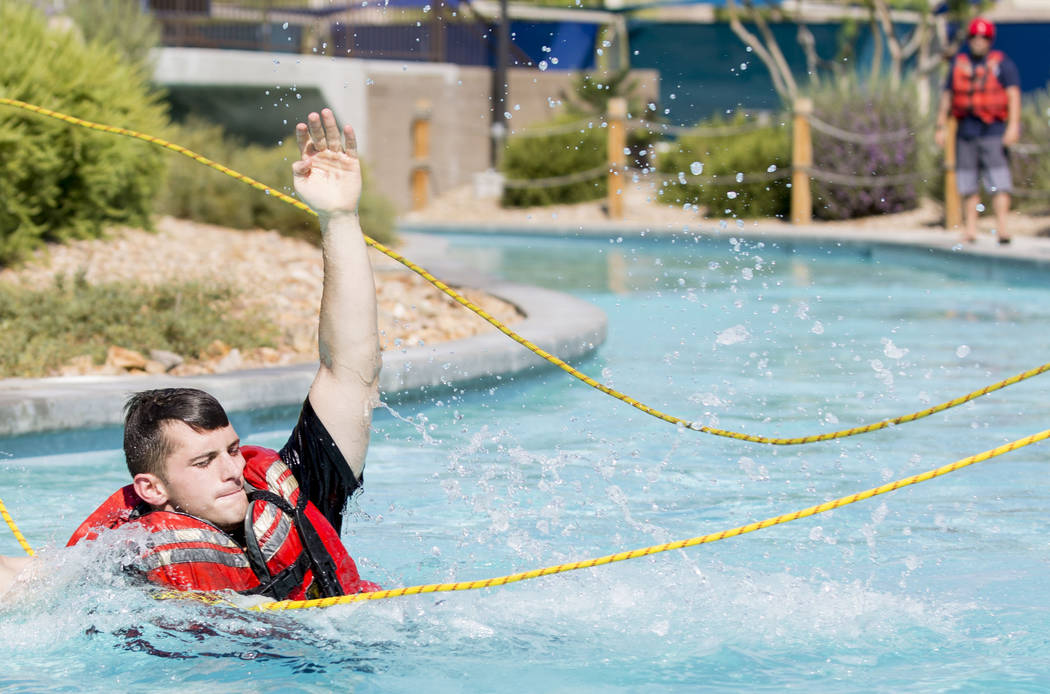 Firefighter Matt Hibschman reaches for ropes during a simulation of a rescue in the wash and churning water conditions at Wet'n'Wild Las Vegas in Las Vegas, Wednesday, June 21, 2017. Elizabeth Bru ...