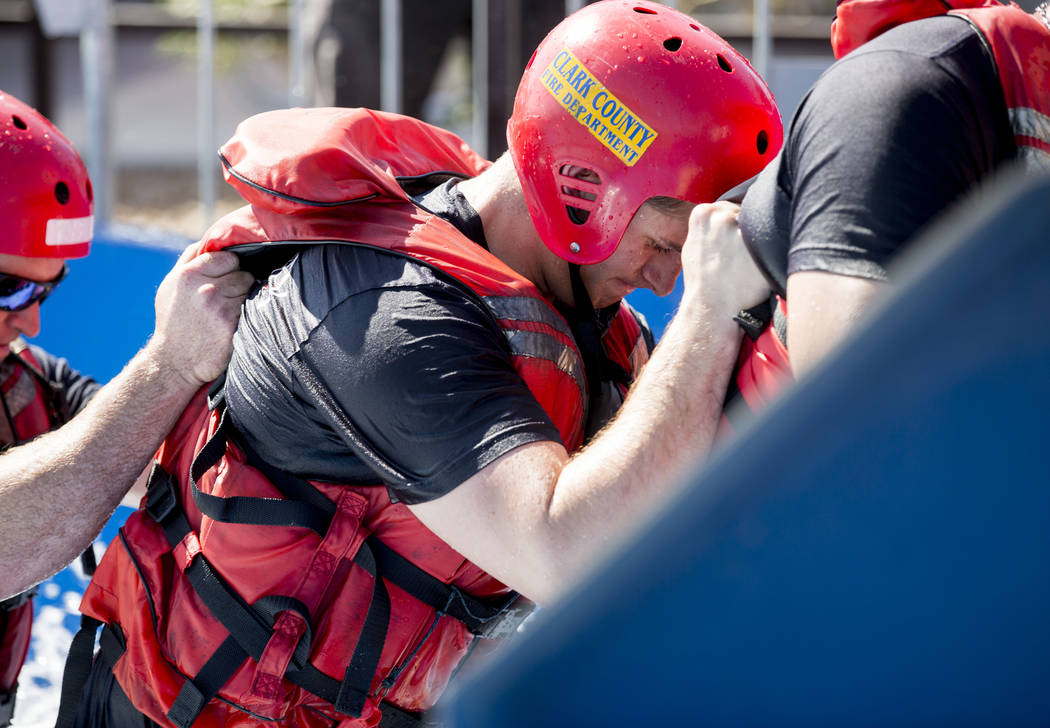Firefighter Matt Hibschman holds onto another firefighter  during a simulation of a rescue in the wash and churning water conditions at Wet'n'Wild Las Vegas in Las Vegas, Wednesday, June 21, 2017. ...