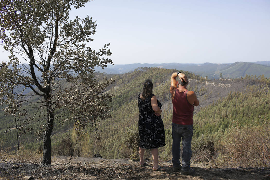A couple standing on top of a hill look at the damage of the forest fire in Serra do Macario, central Portugal, Tuesday, June 20 2017. Emergency services in Portugal said Tuesday they were making  ...