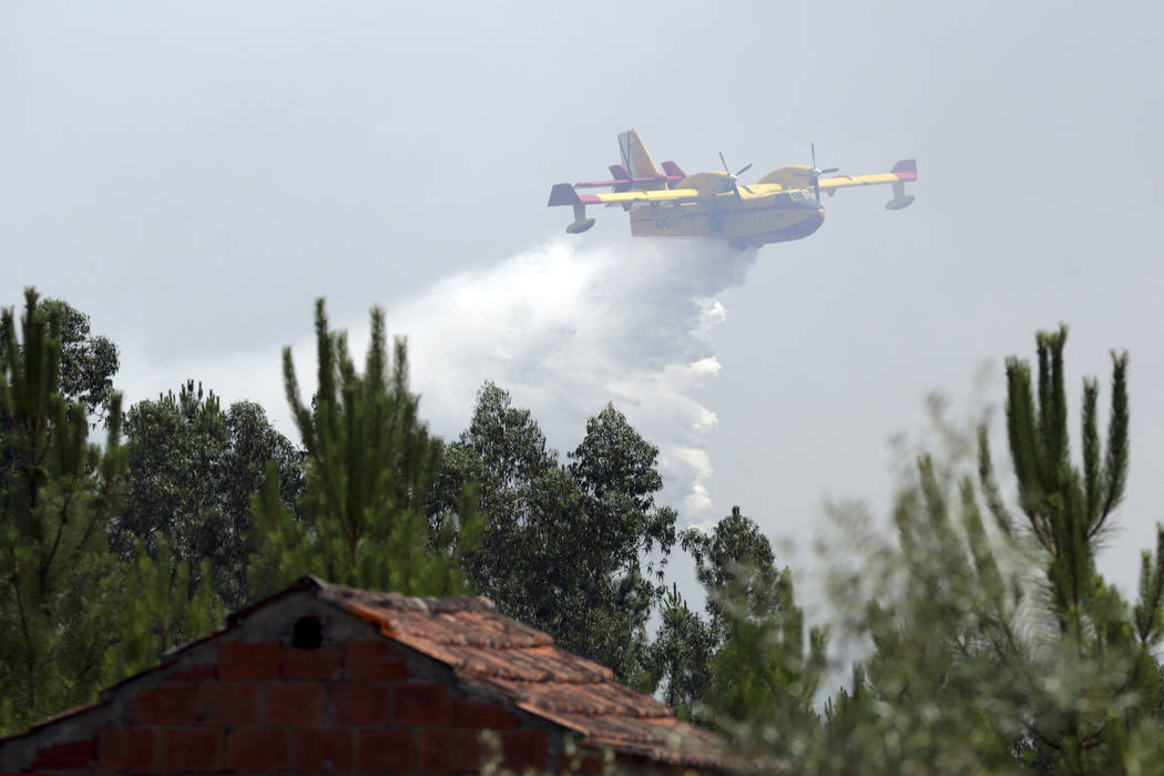 A firefighting airplane drops its load of water trying to prevent a forest fire from reaching the village of Ouzenda, outside Pedrogao Grande, central Portugal, Tuesday, June 20 2017. Ouzenda resi ...