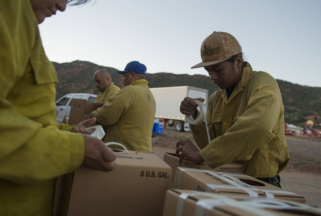 South Piute Agency firefighter Duke Fox prepares water boxes for drinking and other supplies to assist firefighters on the fire line at the Iron County Fairgrounds in Parawan, Utah, Monday, June 1 ...