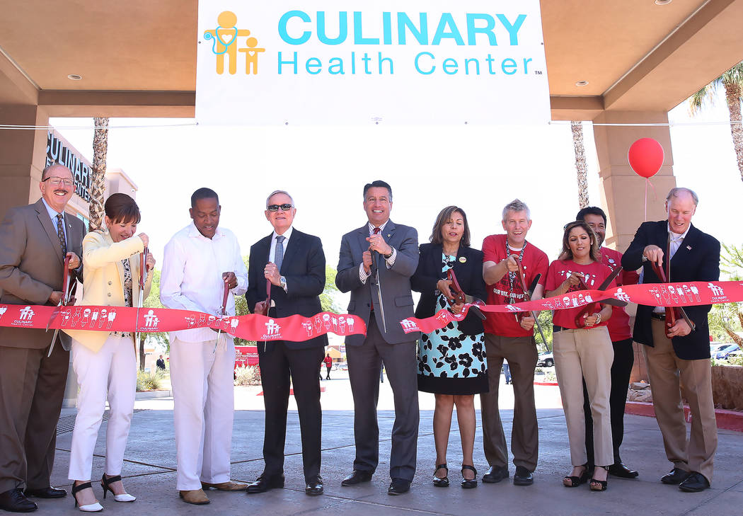 Gov. Brian Sandoval, center, and U.S. Senator Harry Reid,  D-Nevada, fourth left, participated in a ribbon cutting ceremony during the grand opening event of Culinary Health Center on Thursday, Ju ...