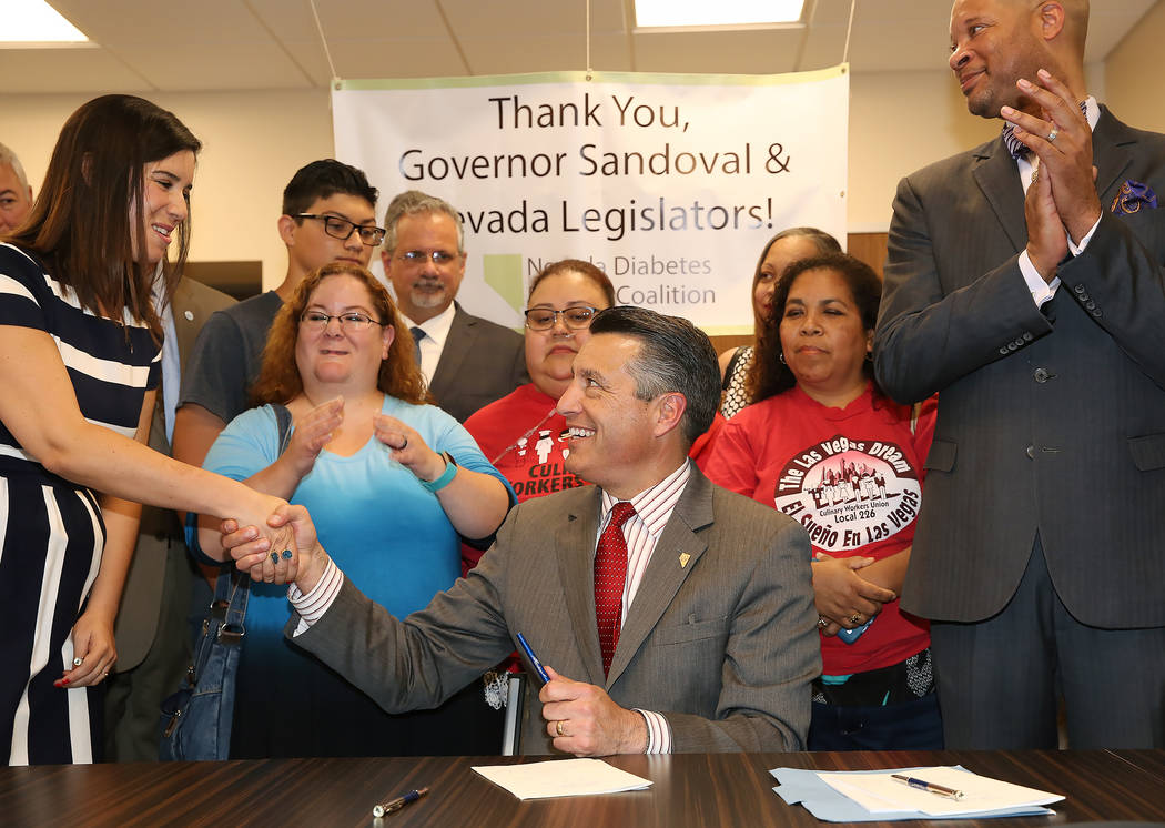 Gov. Brian Sandoval, shakes hands with Sen. Yvanna Cancela, D-Las Vegas, after signing insulin bill, that requires pharmaceutical companies to release insulin prices, into law as Sen. Aaron Ford,  ...