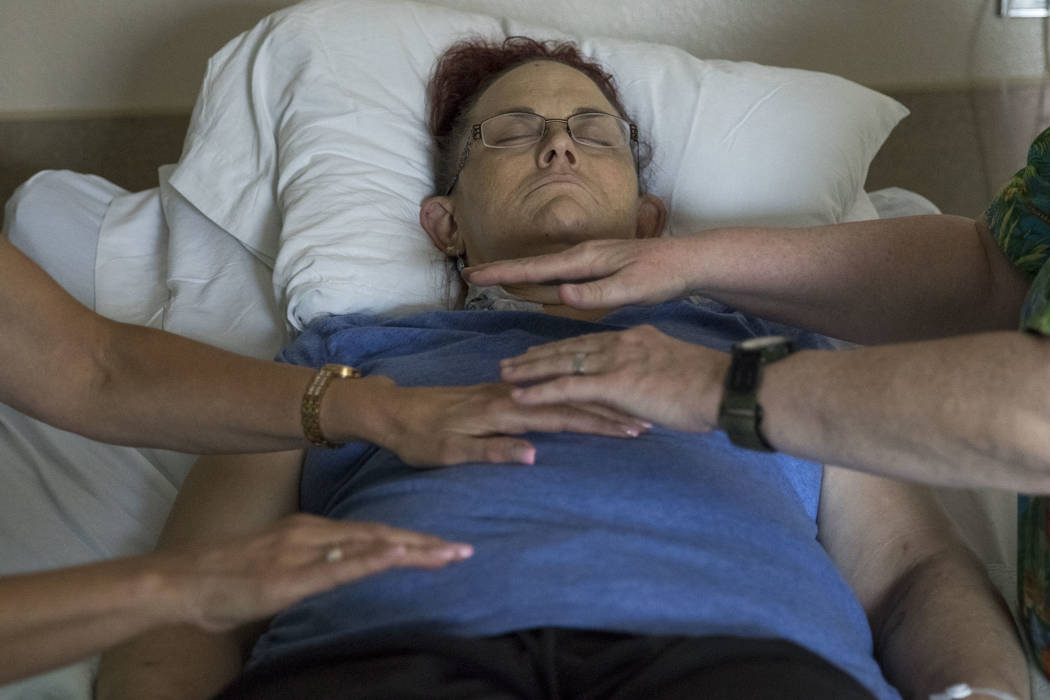 Therese Jones, 43, receives healing touch therapy from integrated therapy nurse Michelle McGrorey and registered nurse Deborah McKinney at UMC in Las Vegas on Wednesday, June 21, 2017. Healing tou ...