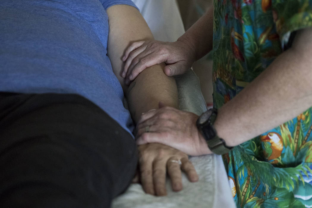 Registered nurse Deborah McKinney, right, administers healing touch therapy to Therese Jones, 43, at UMC in Las Vegas on Wednesday, June 21, 2017. Healing touch therapy is a treatment which attemp ...