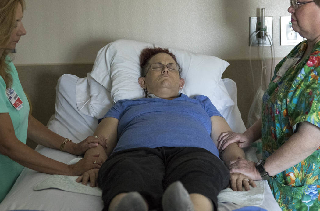 Integrated therapy nurse Michelle McGrorey, left, and registered nurse Deborah McKinney administer healing touch therapy to Therese Jones, 43, at UMC in Las Vegas on Wednesday, June 21, 2017. Heal ...