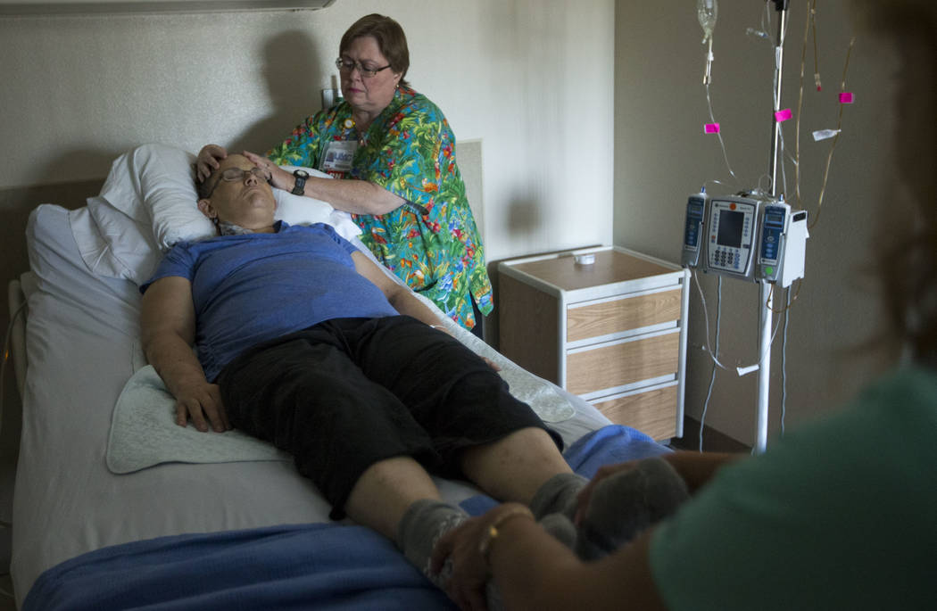 Registered nurse Deborah McKinney, center, and integrated therapy nurse Michelle McGrorey, right, administer healing touch therapy to Therese Jones, 43, at UMC in Las Vegas on Wednesday, June 21,  ...