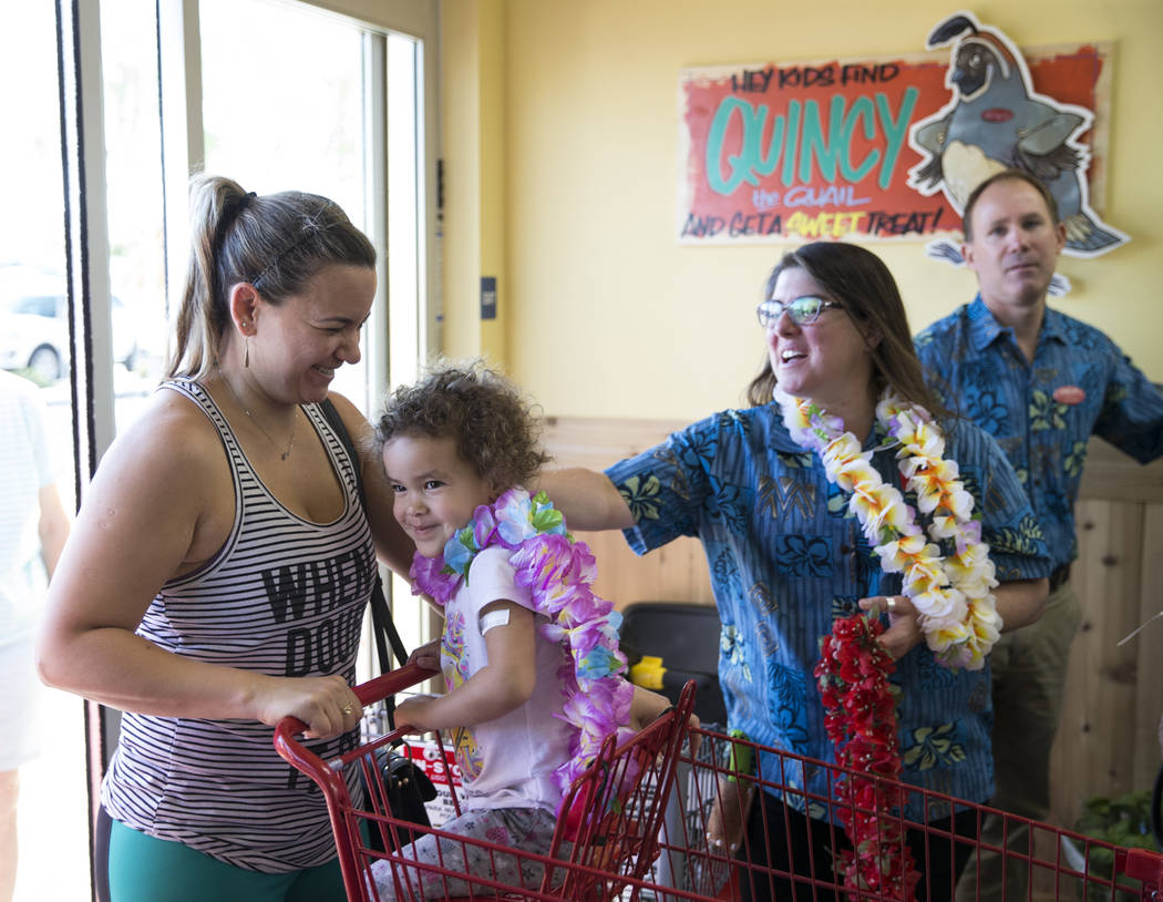 Hebe Soares, left, and her 3-year-old daughter Larissa Andrade, are greeted by store employee Lisa Randles during the grand opening of Trader Joe's, 5639 Centennial Center Blvd., on Friday, June 2 ...