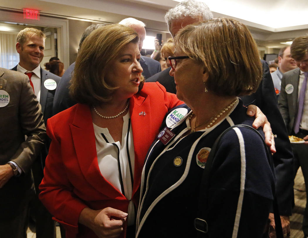 Republican candidate for Georgia's Sixth District Congressional Seat Karen Handel, left, greets supporters at an election-night watch party Tuesday, June 20, 2017, in Atlanta. Handel is in a hotly ...