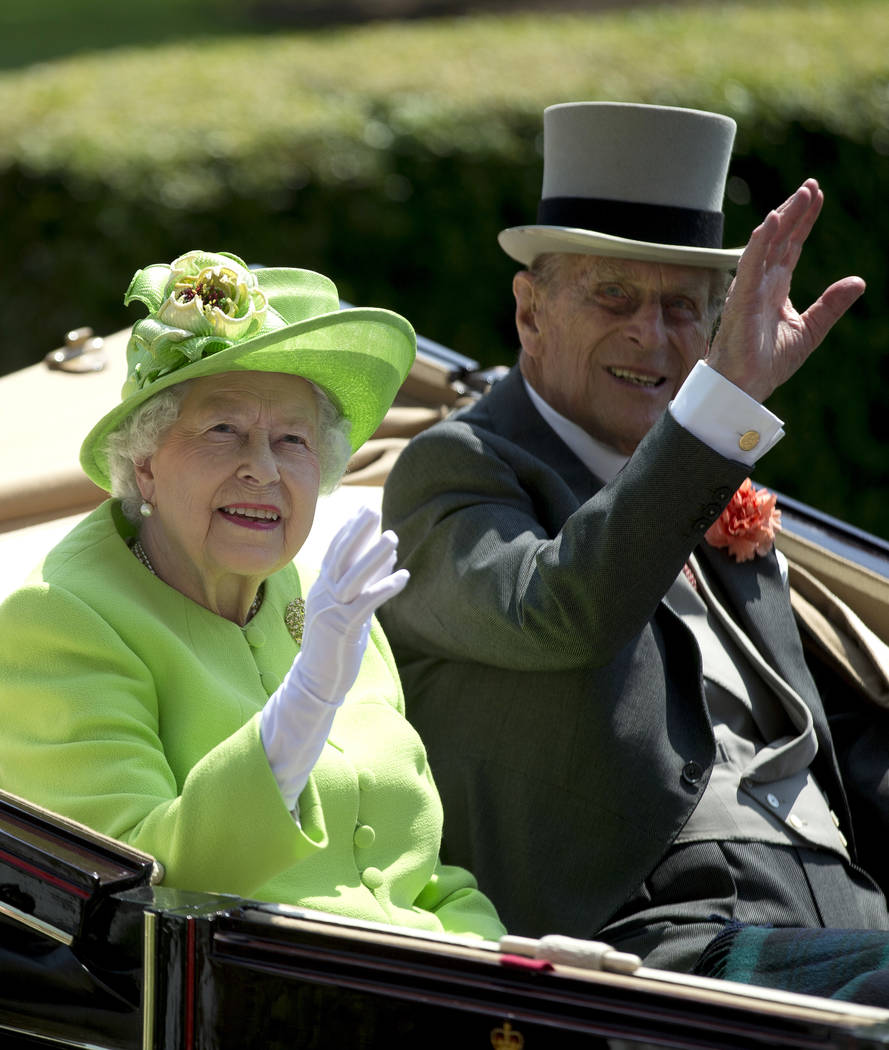 FILE - In this Tuesday, June 20, 2017 file photo, Britain's Queen Elizabeth II, waves to the crowd with Prince Philip, as they arrive by open carriage to the parade ring on the first day of the Ro ...