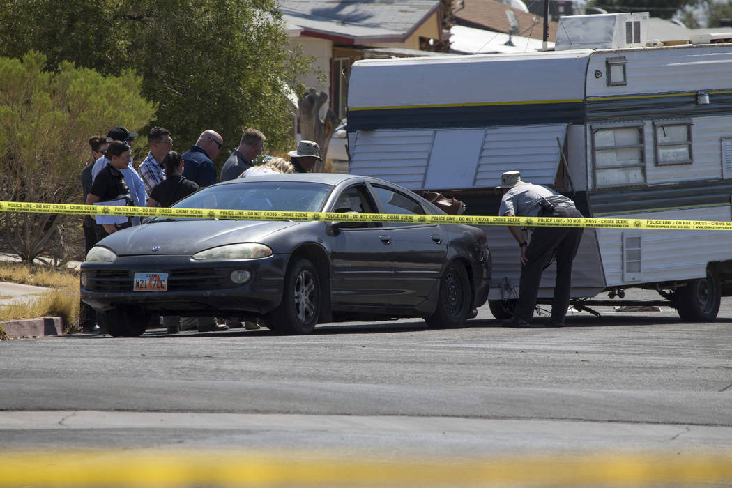 Crime scene personnel look over a vehicle towing a camping trailer that was involved in a fatal crash in the 6500 block of Bourbon Way, near Torrey Pines and Alta drive, on Wednesday, June 20, 201 ...