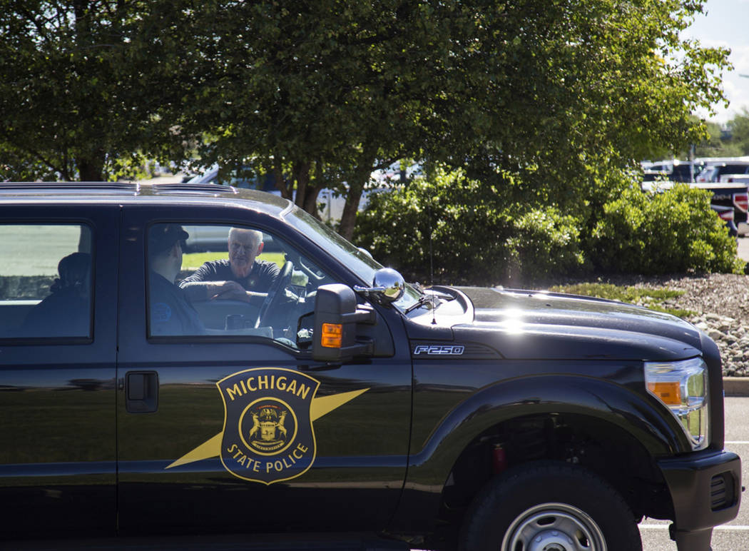 Michigan State Police talk outside Bishop International Airport, Wednesday morning, June 21, 2017, in Flint, Mich. (Shannon Millard/The Flint Journal-MLive.com via AP)