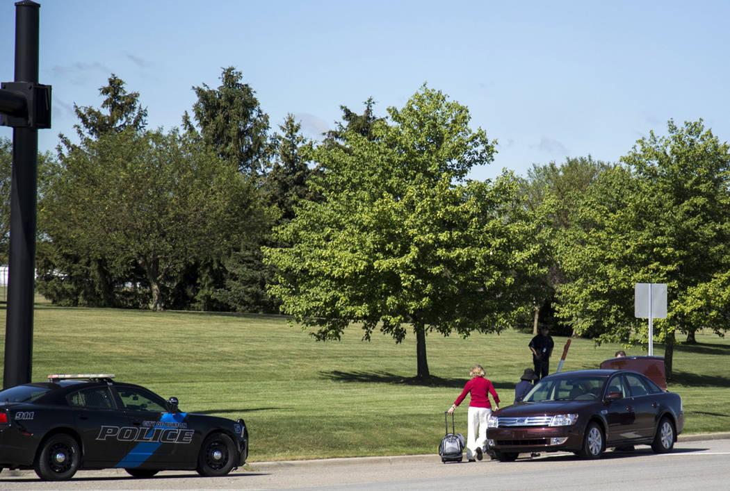 Travellers walk to a car outside Bishop International Airport, Wednesday morning, June 21, 2017, in Flint, Mich. (Shannon Millard/The Flint Journal-MLive.com via AP)