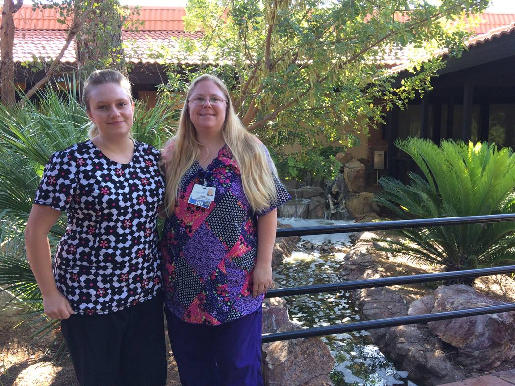 Misty Ashworth, RN, in floral print, and Jade Petersen, certified nurse assistant, pose near the waterfall garden at the Nathan Adelson Hospice facility on Swenson June 6, 2017. Both said there is ...