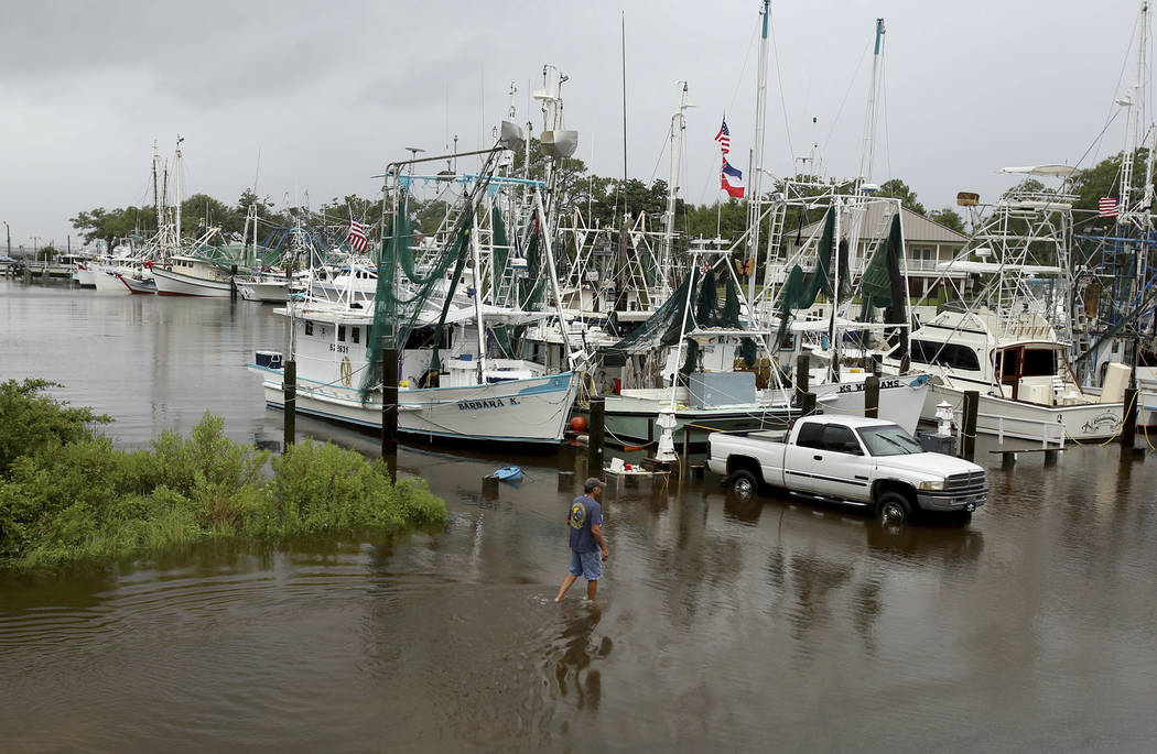 Kenny Kuluz wades through flood waters at the Ocean Springs, Mississippi, harbor as the combination of high tide and the rain bands of Tropical Storm Cindy dumped rain on the Mississippi Gulf Coas ...