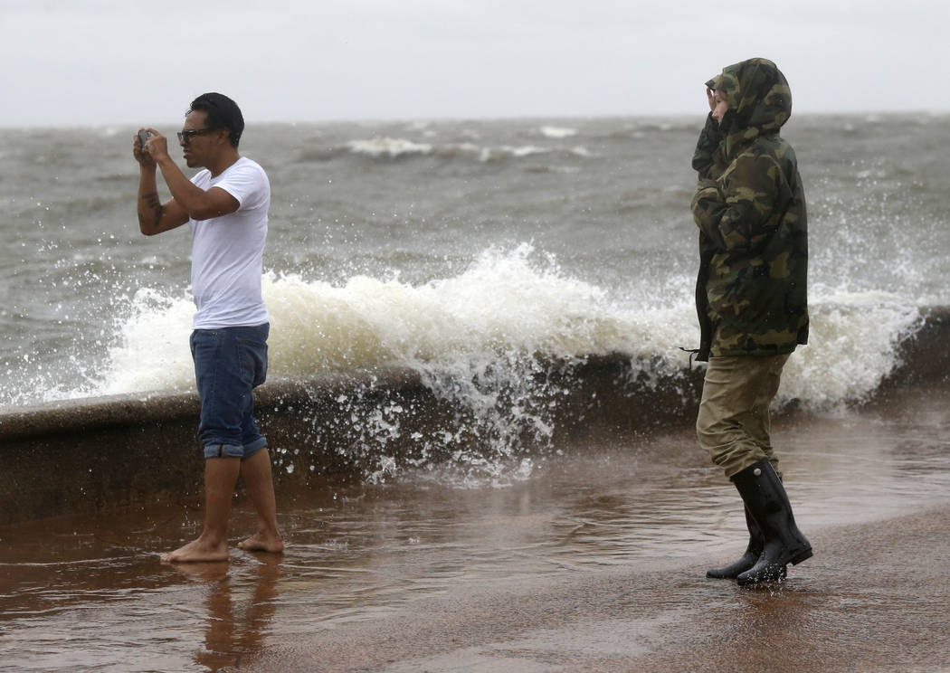 Julie Plaisance, right, and Renee Davila take photos on the shore of Lake Pontchartrain as weather from Tropical Storm Cindy, in the Gulf of Mexico, impacts the region in New Orleans, Tuesday, Jun ...
