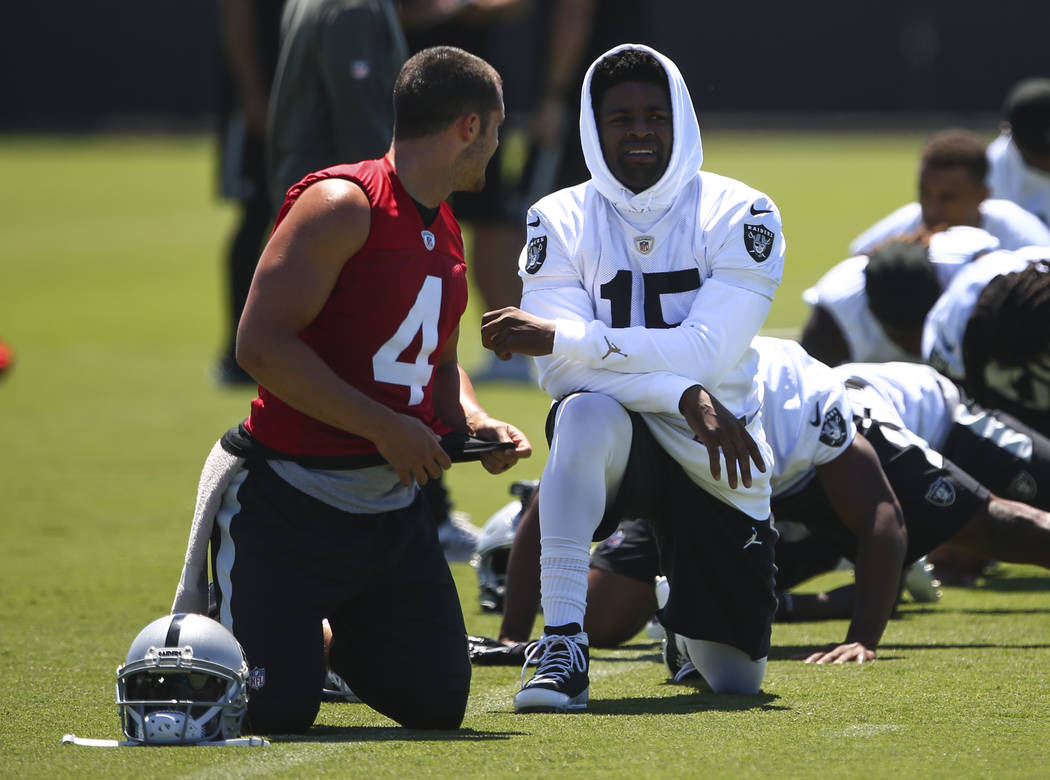 Oakland Raiders quarterback Derek Carr (4) and wide receiver Michael Crabtree (15) talk while warming up during day two of a mini-camp at the Raiders headquarters and training facility in Alameda, ...