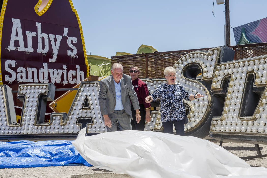 Ava Neidermeyer, a longtime casino employee, celebrates after the unveiling of the Palace Station train and signs, the latest contribution to the Neon Museum, on Thursday, June 22, 2017, with Scot ...