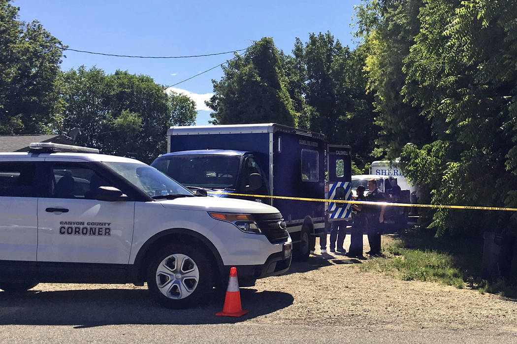 Authorities investigate a scene in Caldwell, Idaho, on Monday, June 19, 2017. Police say three people were found dead inside a home and the Canyon County Sheriff's office is investigating the deat ...