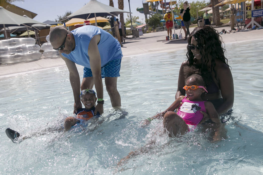 Jamal Williams helps John Coltre, 4, learn to kick, left, while Taraia Williams and Maya Williams, 5, follow along as they attempt to break the world record for largest swimming lesson at Wet 'n'  ...