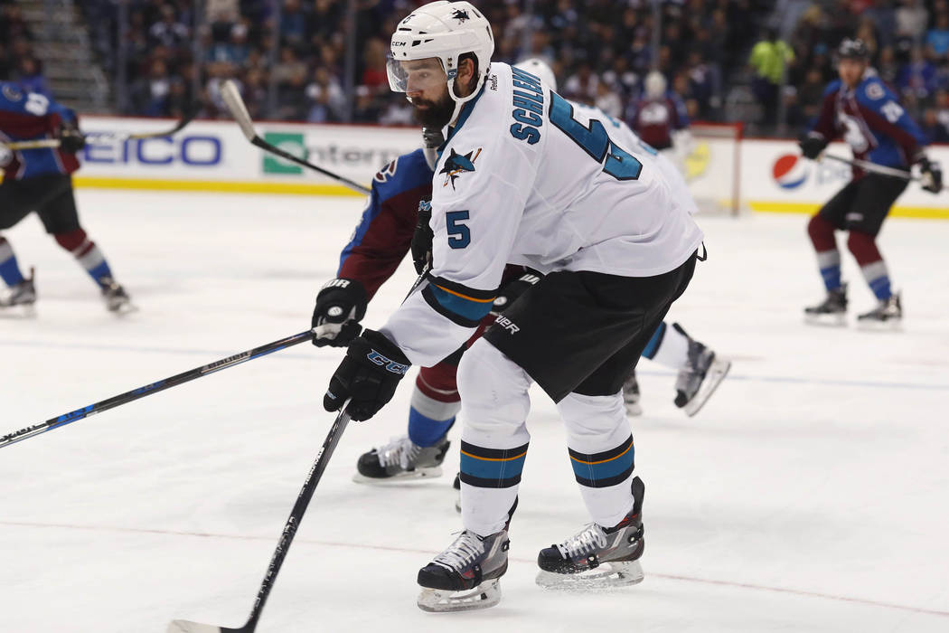 San Jose Sharks defenseman David Schlemko, front, clears the puck as Colorado Avalanche left wing Gabriel Landeskog, of Sweden, defends in the first period of an NHL hockey game Monday, Jan. 23, 2 ...