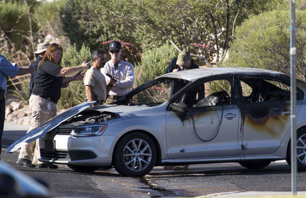 Crime scene personnel and detectives investigate a burned car that contained a body in the 6600 block of Castor Tree Way, near Rainbow Boulevard and Cheyenne Avenue, on Thursday, June 21, 2017. (R ...
