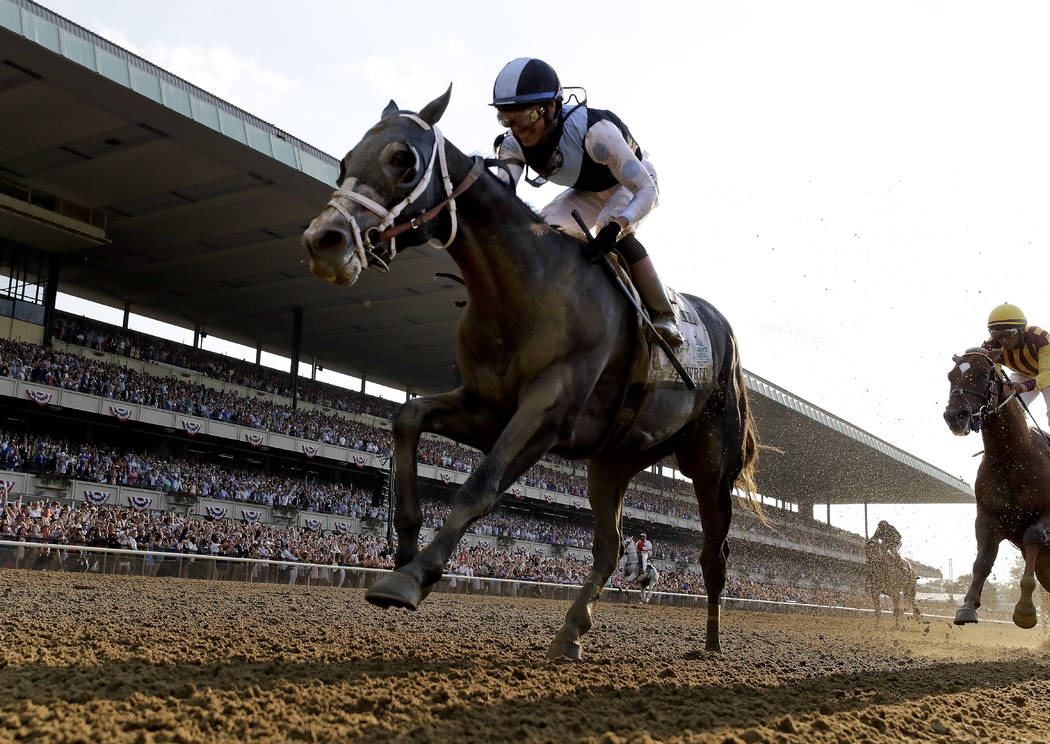 Tapwrit, ridden by Jose Ortiz crosses the finish line to win the 149th running of the Belmont Stakes horse race, Saturday, June 10, 2017, in Elmont, N.Y. Irish War Cry, right, finished second. (AP ...