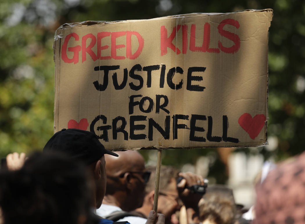 A protester holds a sign demanding justice for the victims of the deadly fire at Grenfell Tower apartment block as people gather in central London on Wednesday June 21, 2017. Activists are plannin ...