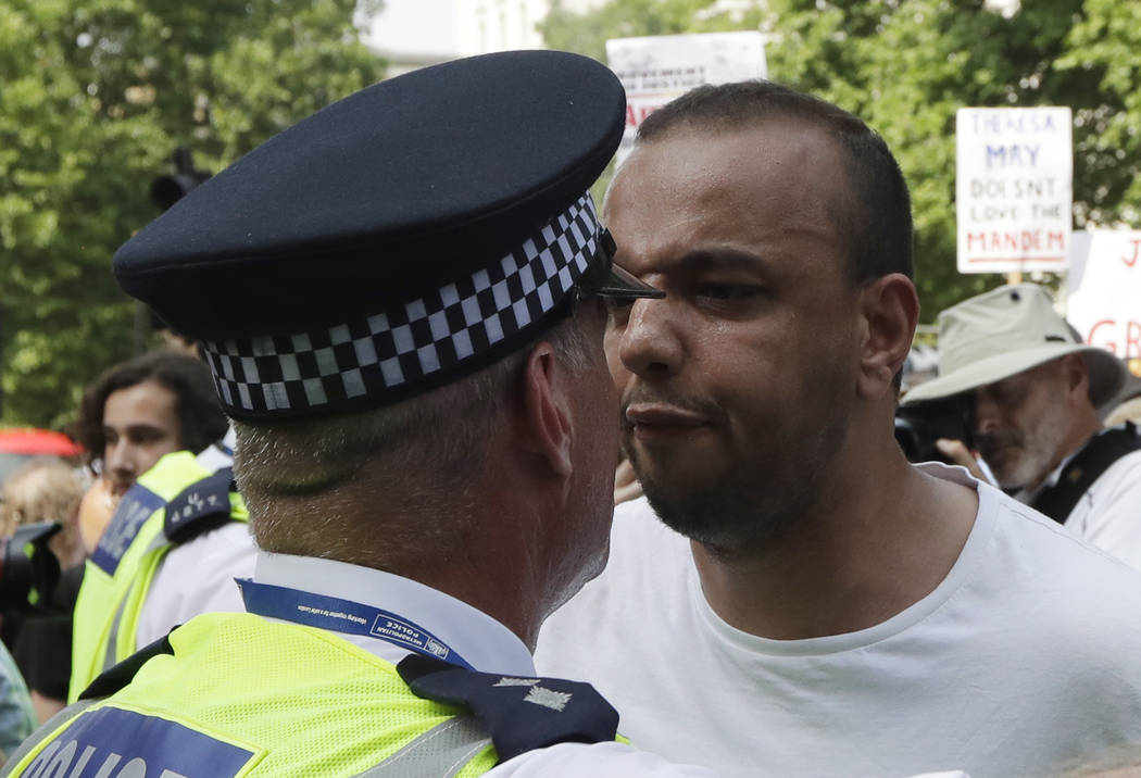 A demonstrator confronts a police officer as they demand justice for the victims of the recent deadly apartment block fire at Grenfell Tower, as they march towards parliament in central London Wed ...