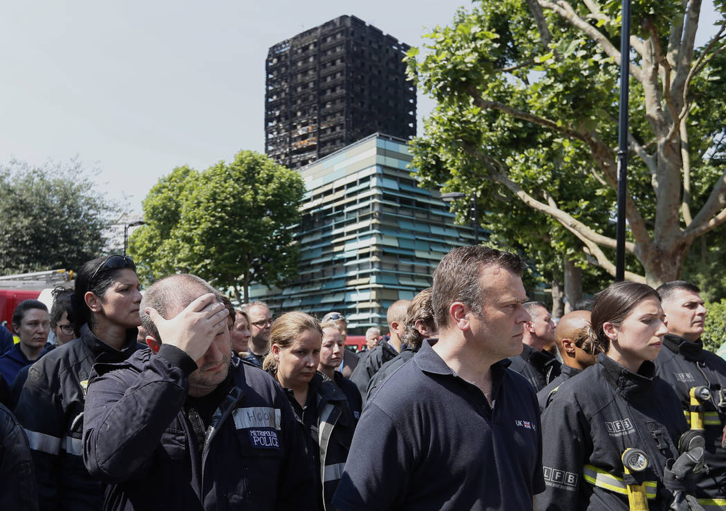 Emergency services workers take part in a minute's silence in front of Grenfell Tower in London, Monday, June 19, 2017. Tens of people died when a fire engulfed the high-rise apartment block in we ...