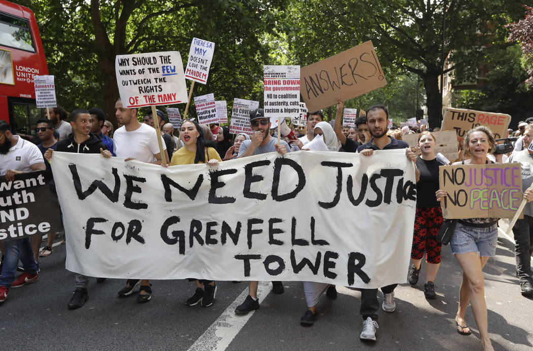 Demonstrators hold a banner demanding justice for the victims of the recent deadly apartment block fire at Grenfell Tower, as they march towards parliament in central London on Wednesday June 21,  ...