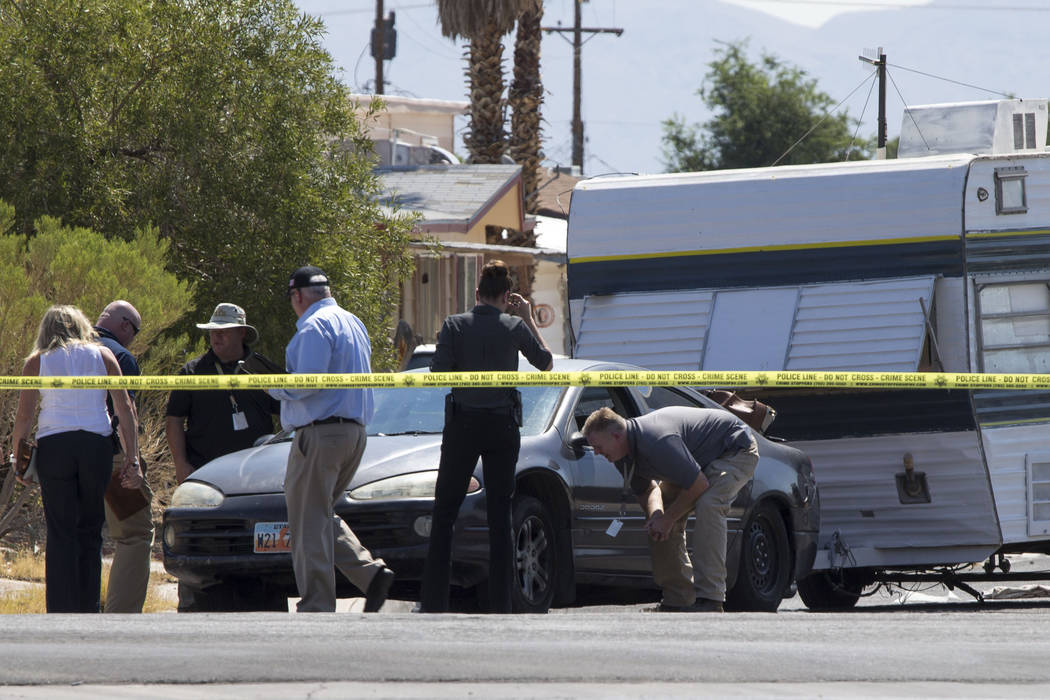 Crime scene personnel look over a vehicle towing camping trailer that was involved in a fatal incident at the 6500 block of Bourbon Way, near Torrey Pines and Alta, on Wednesday, June 20, 2017. A  ...