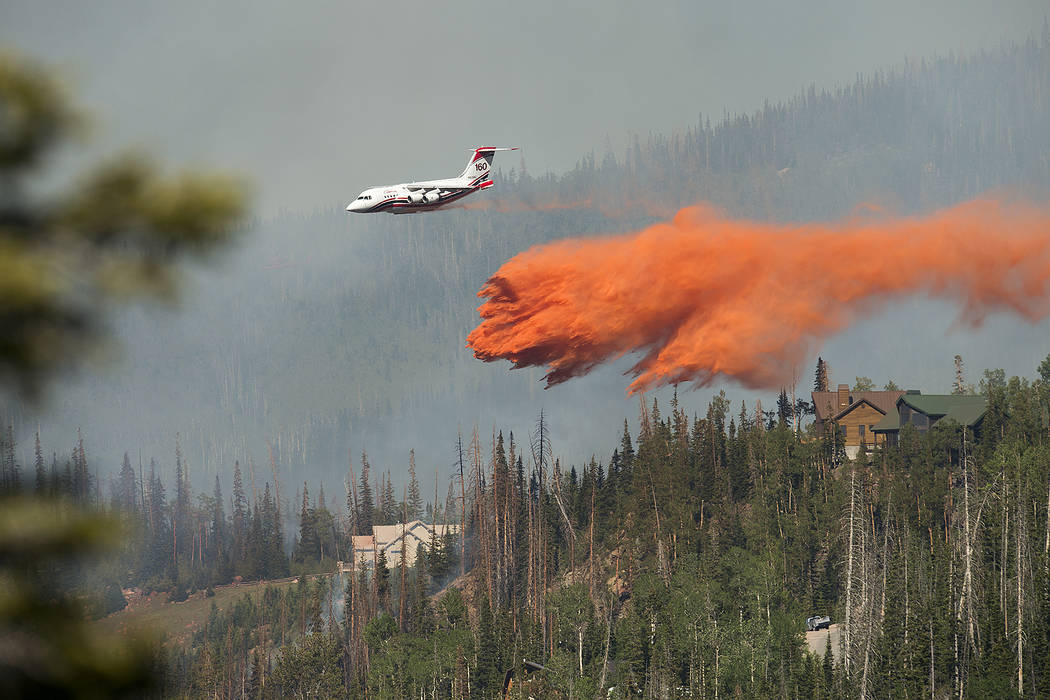 A plane drops fire retardant as a wildfire burns Sunday, June 18, 2017, along the Steam Engine area near the southern Utah ski town of Brian Head, Utah. (Leah Hogsten/The Salt Lake Tribune via AP)