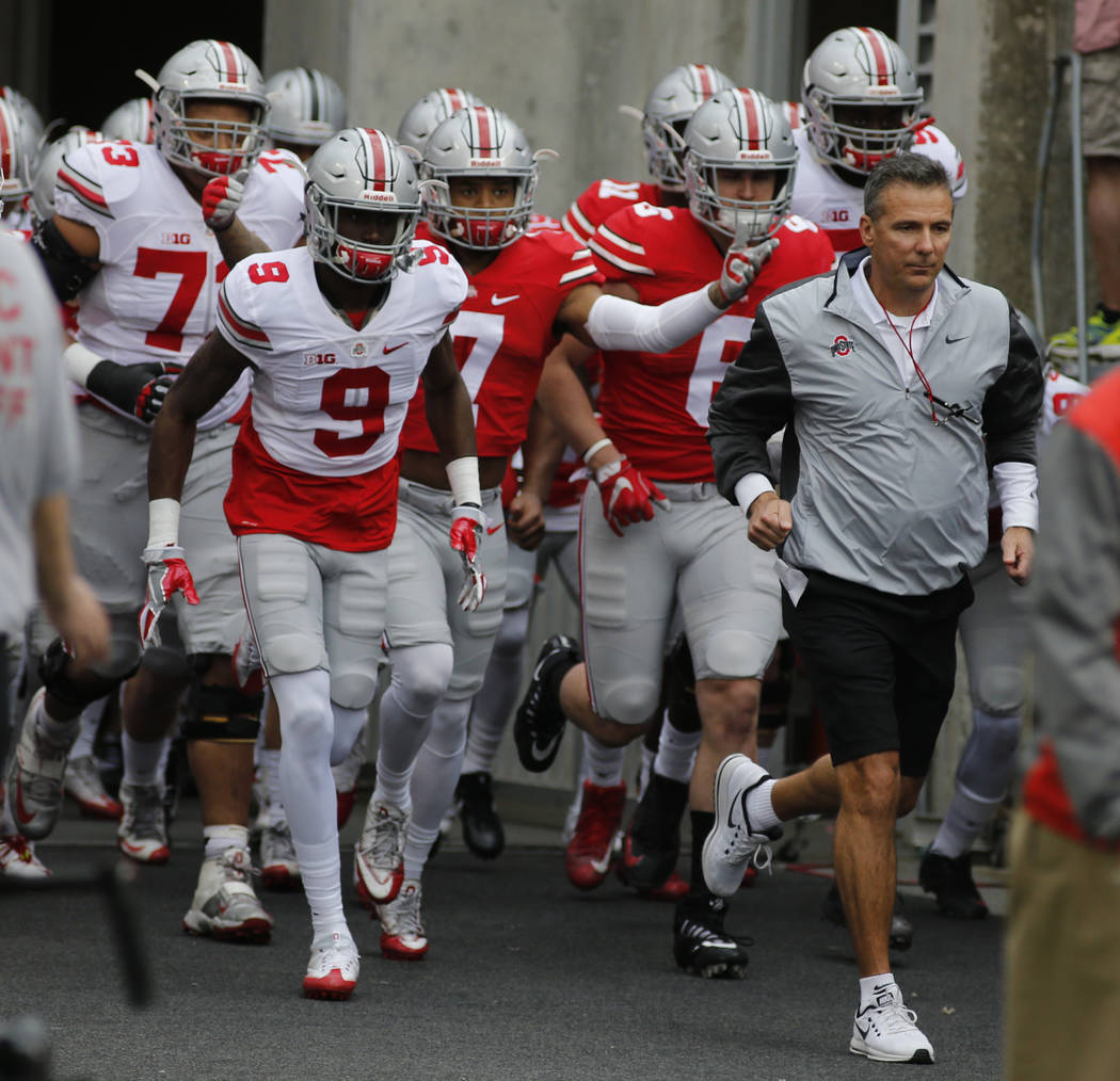 Ohio State head coach Urban Meyer leads his team on to the field for their NCAA college spring football game Saturday, April 15, 2017, in Columbus, Ohio. (AP Photo/Jay LaPrete)