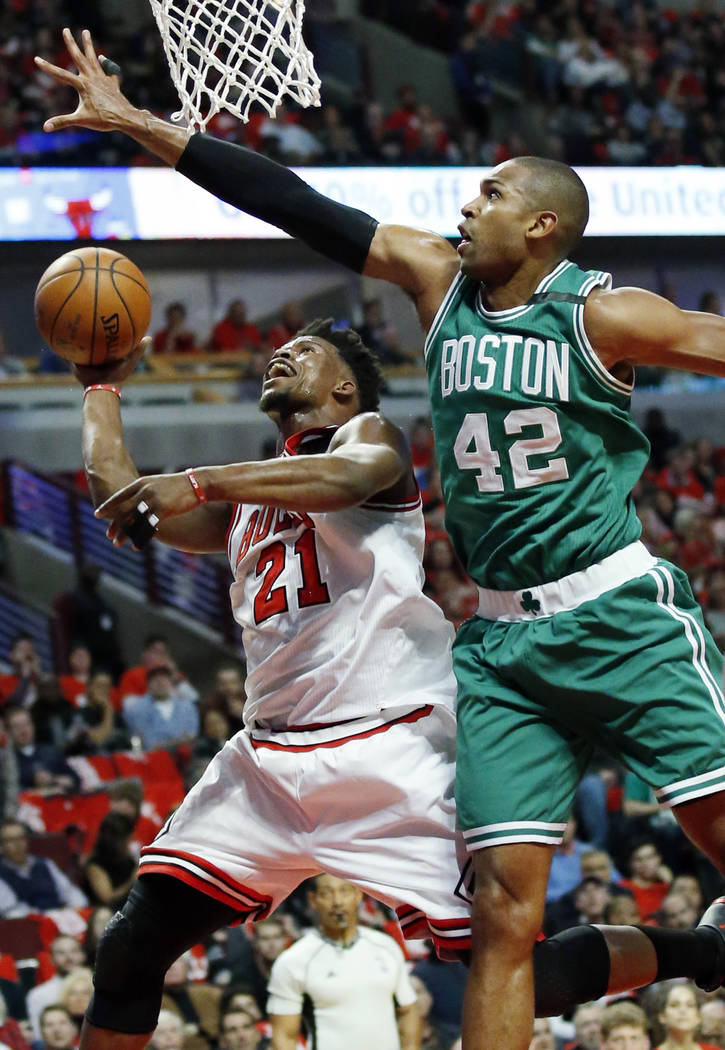 Chicago Bulls' Jimmy Butler, left, drives to the basket against Boston Celtics' Al Horford during the first half in Game 6 of an NBA basketball first-round playoff series, Friday, April. 28, 2017, ...
