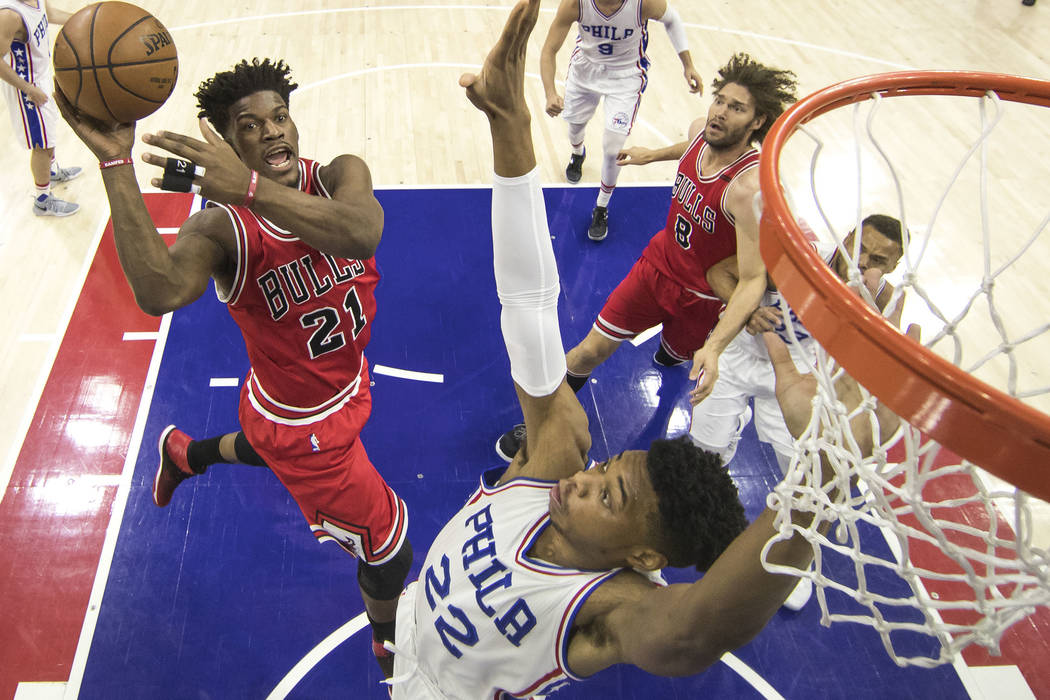 Chicago Bulls' Jimmy Butler, left, goes up for the shot with Philadelphia 76ers' Richaun Holmes, right, defending the basket during the first half of an NBA basketball game, Thursday, April 6, 201 ...