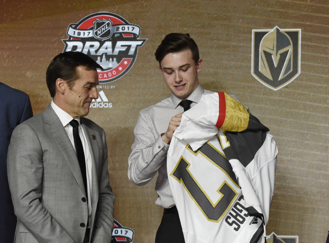 June 23, 2017; Chicago, IL, USA; Cody Glass puts on a team jersey after being selected as the number six overall pick to the Vegas Golden Knights in the first round of the 2017 NHL Draft at the Un ...