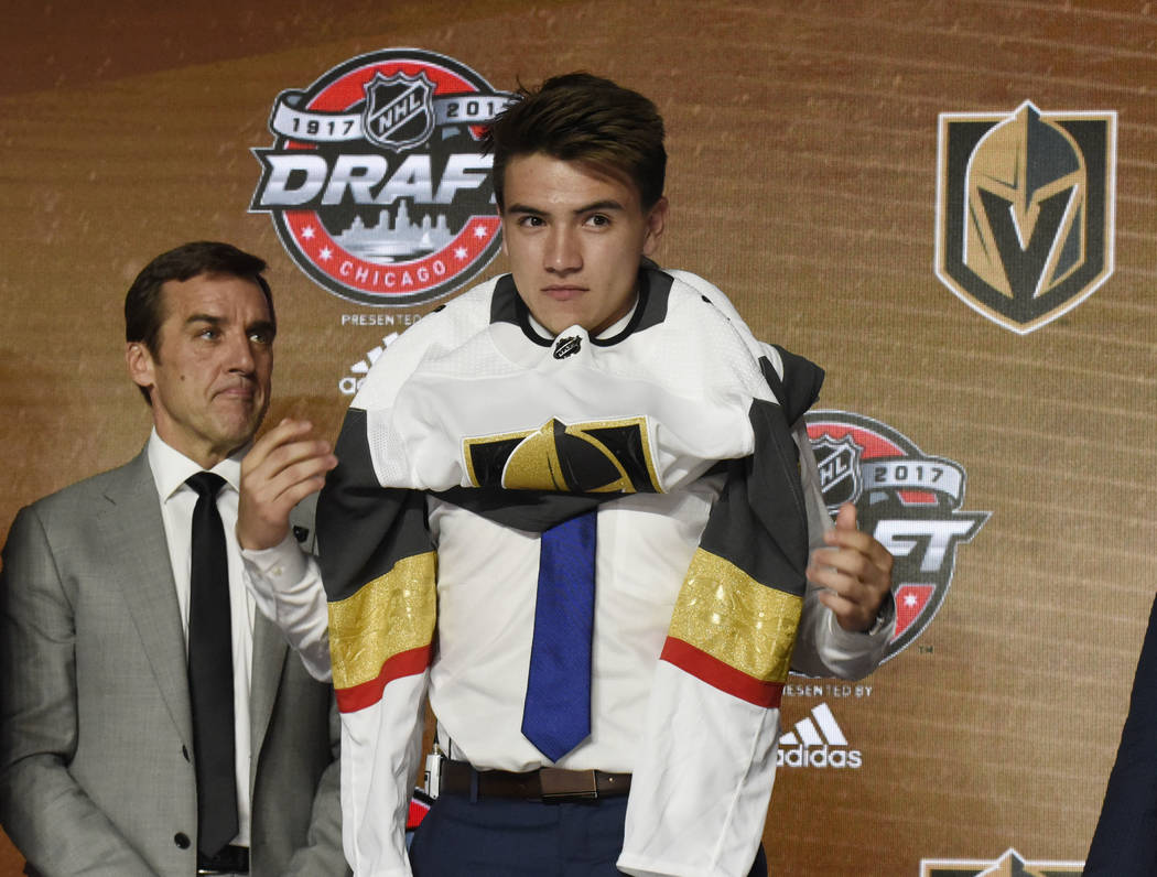 June 23, 2017; Chicago, IL, USA; Nick Suzuki puts on a team jersey after being selected as the number thirteen overall pick to the Vegas Golden Knights in the first round of the 2017 NHL Draft at  ...