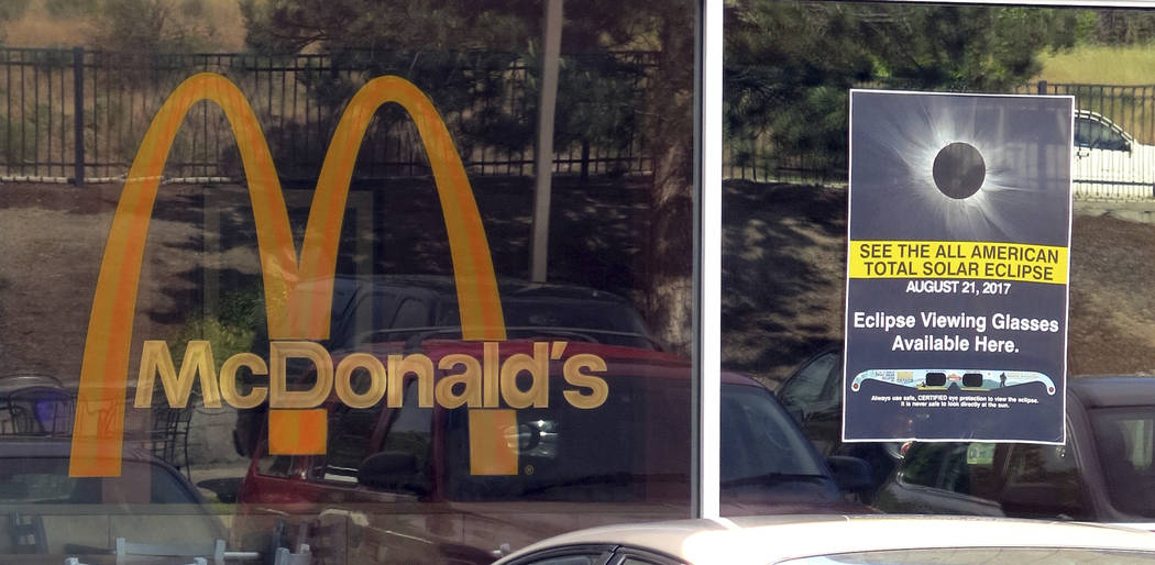 A poster advertising the Aug. 21, 2017, total solar eclipse hangs in the window of a McDonald's restaurant in Madras, Oregon on June 12, 2017. The first place to experience total darkness as the m ...