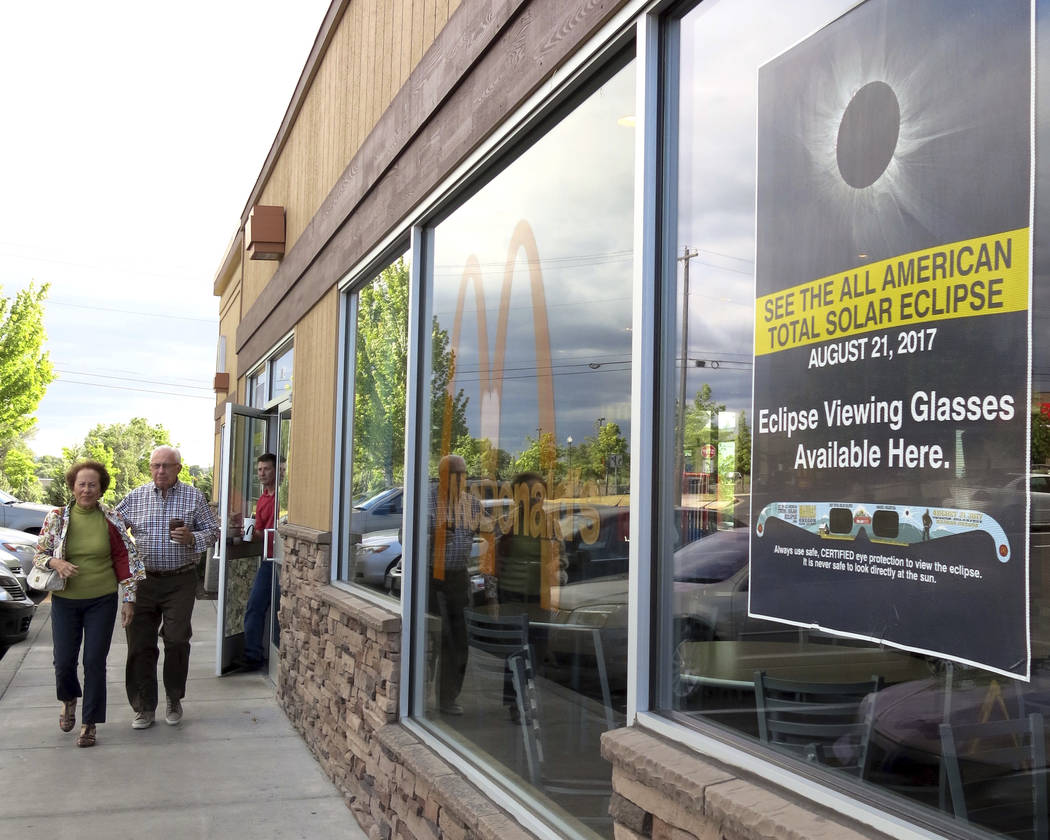 A poster advertising the Aug. 21 total solar eclipse hangs in the window of a McDonald's restaurant in Madras, Oregon on June 12, 2017. The first place to experience total darkness as the moon pas ...