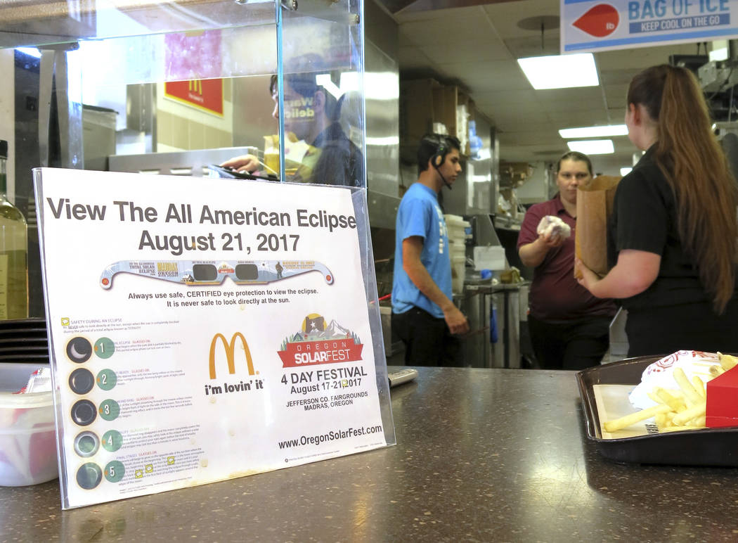 A sign advertising solar eclipse glasses for the Aug. 21, 2017, total solar eclipse hangs in the window of a McDonald's restaurant in Madras, Oregon on June 12, 2017. The first place to experience ...