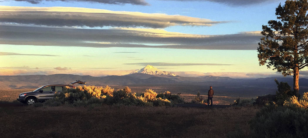 Joe Krenowicz, executive director of the Madras-Jefferson County Chamber of Commerce, looks toward Mt. Jefferson as the sun rises over Madras, Oregon on June 13, 2017. The first place to experienc ...