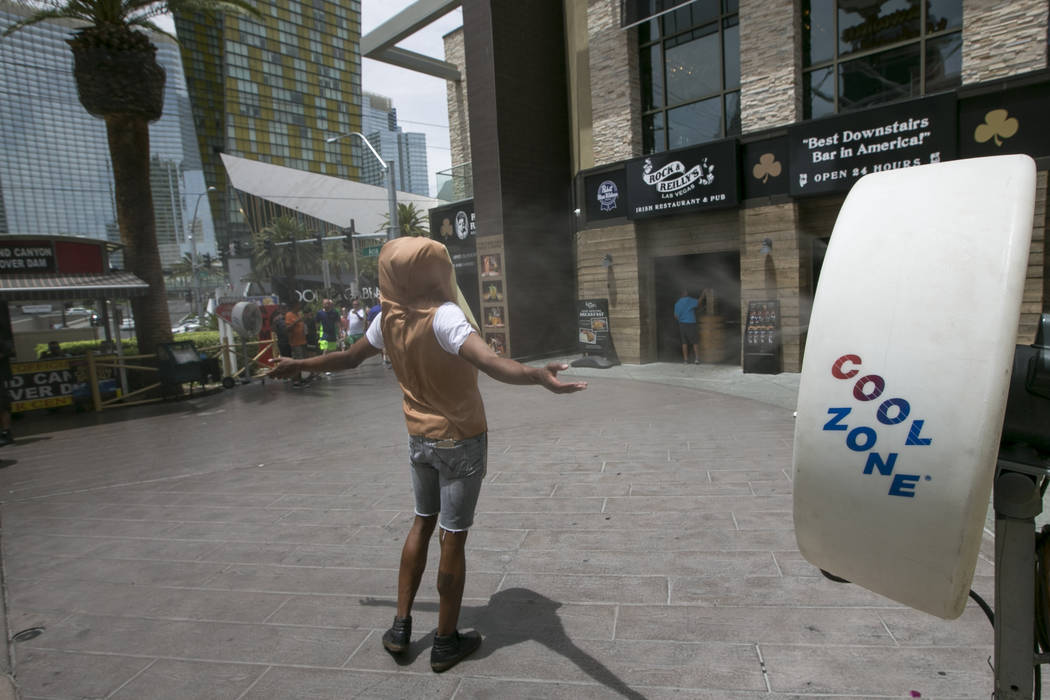 A man in a hot dog bun costume cools off in front of a misting fan on the Las Vegas Strip on Thursday, June 8, 2017. (Richard Brian/Las Vegas Review-Journal) @vegasphotograph