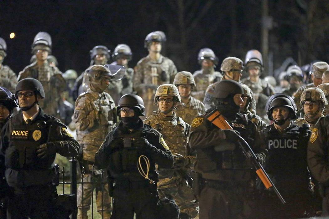 In this Friday, Nov. 28, 2014, file photo, police and Missouri National Guard stand guard as protesters gather in front of the Ferguson Police Department. The family of Michael Brown, who was kill ...