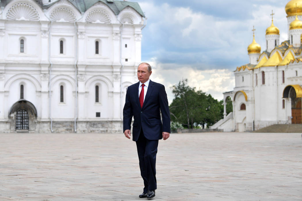 Russian President Vladimir Putin walks along the Cathedral Square of the Kremlin to take part in a holiday reception in Moscow, Monday, June 12, 2017.  (Alexei Druzhinin/Sputnik, Kremlin Pool Phot ...